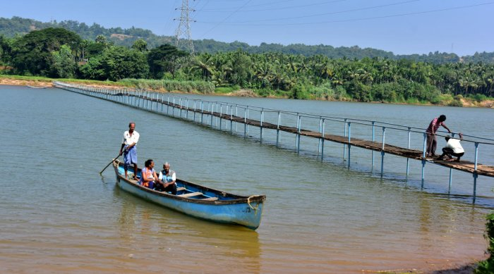 Residents of Pavoor-Uliya cross River Nethravathi through a boat.