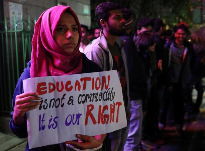 A student holds a placard at a human chain formation to protest against a proposed fee hike in Jawaharlal Nehru University (JNU), in New Delhi. Photo by REUTERS