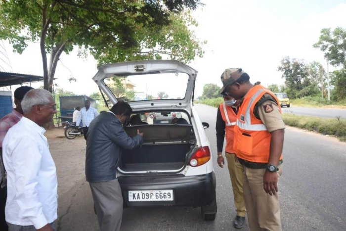 Police and poll officials inspect a car, intercepted at a checkpost, under Hunsur Assembly segment in Mysuru district, recently. dh photo