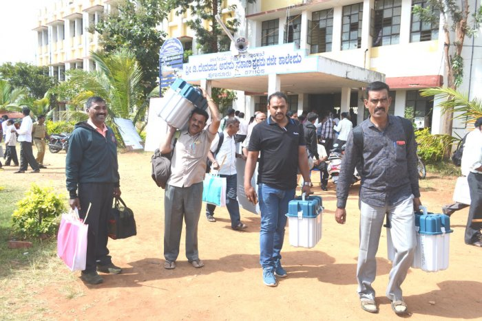 Poll officials, carrying Electronic Voting Machines (EVMs), leave for their respective polling centres in Hunsur Assembly segment, after the mustering process at D Devaraj Urs First Grade College in Hunsur, Mysuru district on Wednesday. dh photo