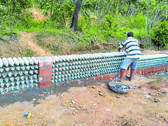 A compound wall at Injadi in Subrahmanya Gram Panchayat is being constructed using waste plastic water bottles.