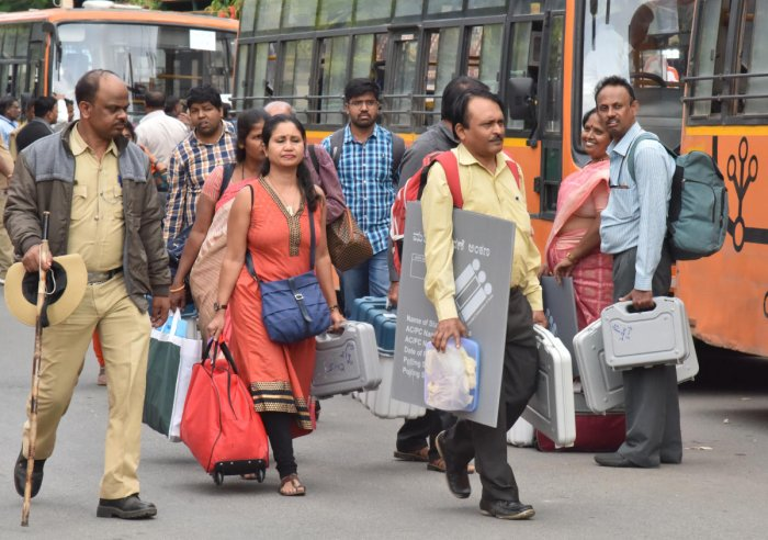 Officials head to a polling booth in Bengaluru on Wednesday. DH Photo/Janardhan B K