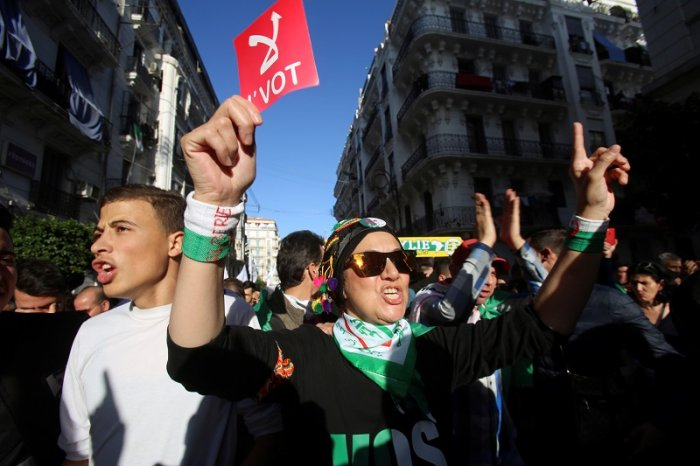 """A demonstrator holds a sign reading """"No vote"""" as she takes part in a protest to demand for the presidential election scheduled for next week to be cancelled, in Algiers, Algeria. (Reuters Photo)"""