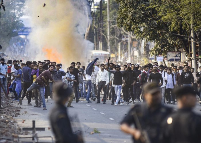 Protestors throw stones as they clash with the police during their march against the Citizenship (Amendment) Bill. Photo by PTI.