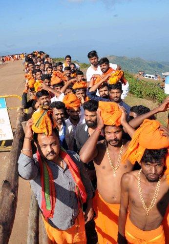 Devotees waiting in a queue at the entrance of Sri Guru Dattatreya Bababudan Swamy Dargah in Chikkamagaluru taluk on Thursday.