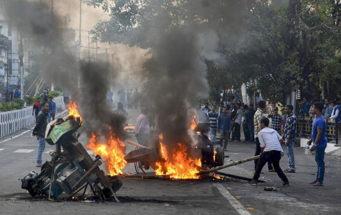 Protesters burn machinery to block a road during an agitation against the Citizenship Amendment Bill in Guwahati on Thursday. PTI