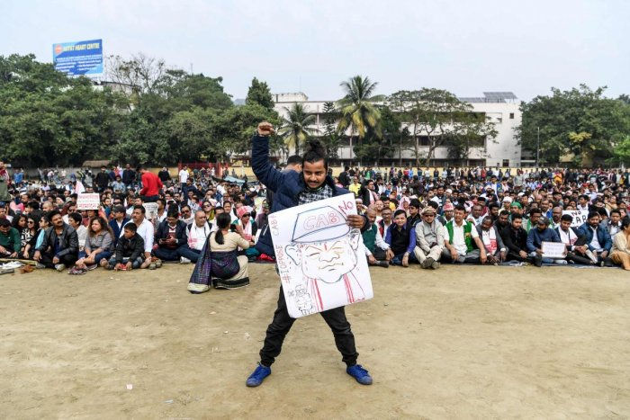 A demonstrator (C) holds a placard displaying a drawing of Assam Chief Minister Sarbananda Sonowal as others sit in the background during a protest against the government's Citizenship Amendment Bill (CAB) in Guwahati on December 13, 2019. (Photo by AFP)