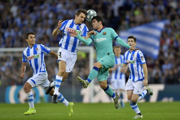 Barcelona's Carles Alena, center right, jumps for the ball with Real Sociedad's Diego Llorente during the Spanish La Liga soccer match between Real Sociedad and Barcelona, at Anoeta stadium, in San Sebastian. (AP Photo)