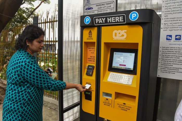 People paying in pay machine at Smart Car Parking trail work is going on by BBMP maintain by Central Parking Services at Kasturba Road in Bengaluru on Saturday. Photo by S K Dinesh