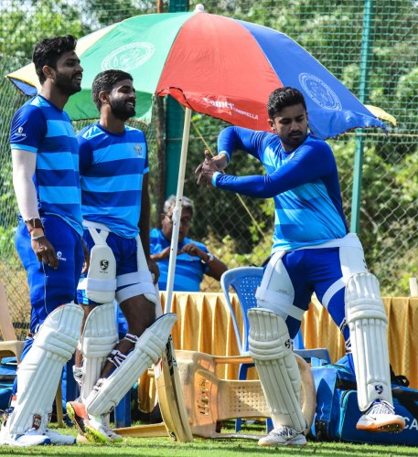 Karnakata stand-in skipper Karun Nair demonstrates a shot as Rohan Kadam (left) and R Samarth look on during a practice session in Hubballi on Monday. DH Photo/ Tazuddin Azad