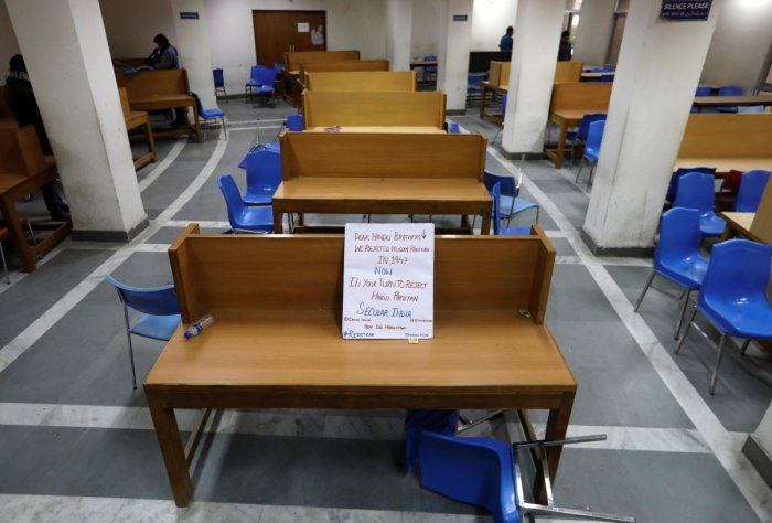 A placard lies on a table inside a partially damaged library of the Jamia Millia Islamia university after police entered the university campus on the previous day, following a protest against a new citizenship law. Reuters