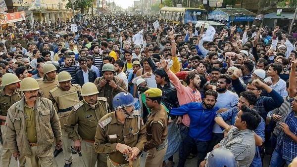 Police keep a watch as Muslim people shout slogans during a protest against Citizenship Amendment Act, at Mirza Hadipur Chowk in Mau, Monday, Dec. 16, 2019. (PTI Photo)