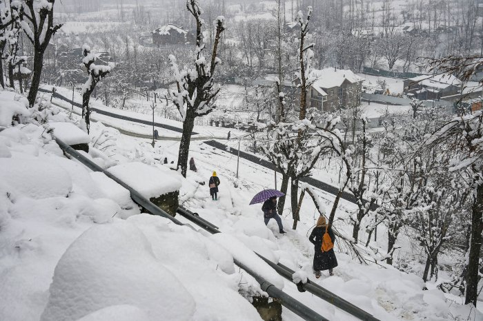 People on a snow-covered path to climb up hill during snowfall, on the outskirts of Srinagar. (PTI Photo)