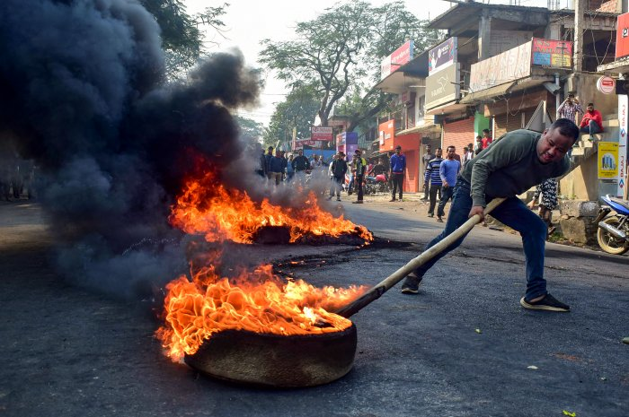 A demonstrator burns tyres on National Highway 17 during a protest rally against CAB, at Boko in Kamrup district of Assam. (PTI Photo)