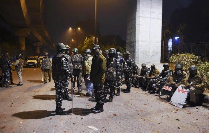 Policemen stand guard near Jamia Millia Islamia following the protests against Citizenship Amendment Act, in New Delhi. (PTI Photo)