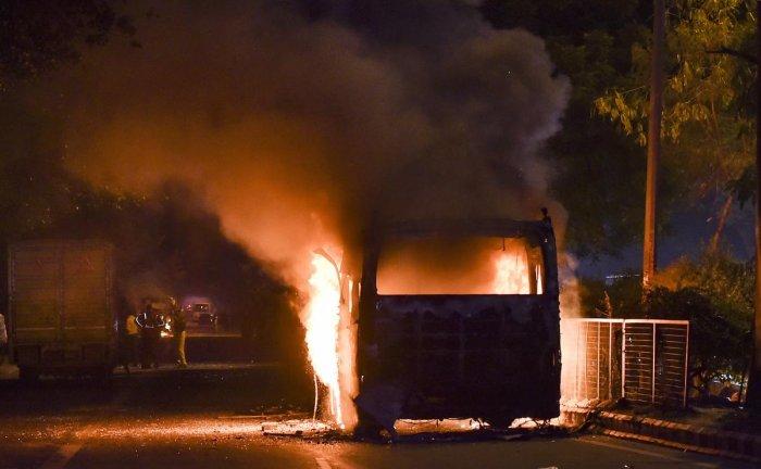 bus set ablaze by protestors against the Citizenship Amendment Act at Mathura Road, in New Delhi. PTI