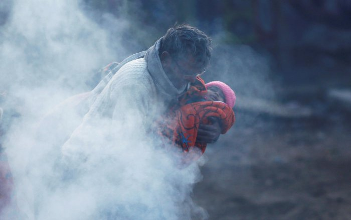 A man holding a baby wrapped in a blanket stands next to a bonfire on a cold winter morning in New Delhi. (Photo by Reuters)
