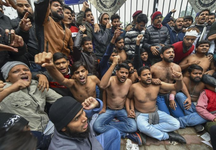 A group of Jamia Millia students stood shirtless in the bone-chilling cold outside the university gates on Monday and formed a human chain to protest the police action against their colleagues a day earlier. Photo/PTI
