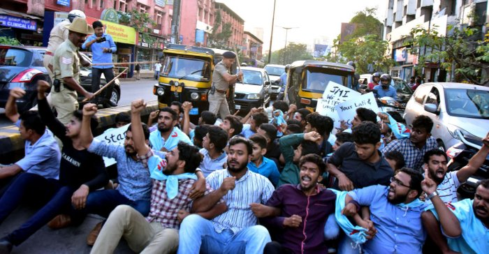 Police use mild force on the activists of Campus Front of India who resorted to sudden protest by blocking road at Balmatta Junction in Mangaluru on Monday. DH Photo