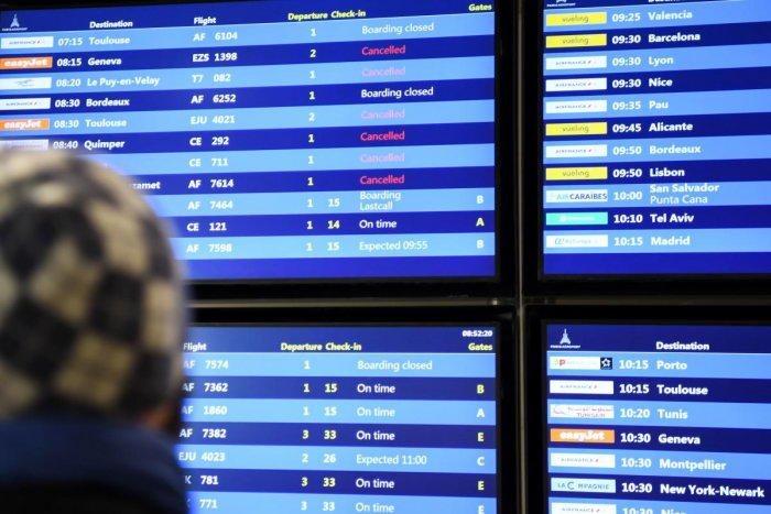 In this file photo taken on December 5, 2019 a man looks at the information board reading the different planes cancelled during a strike over French government's plan to overhaul the country's retirement system, at the Paris Orly airport in Orly, as part
