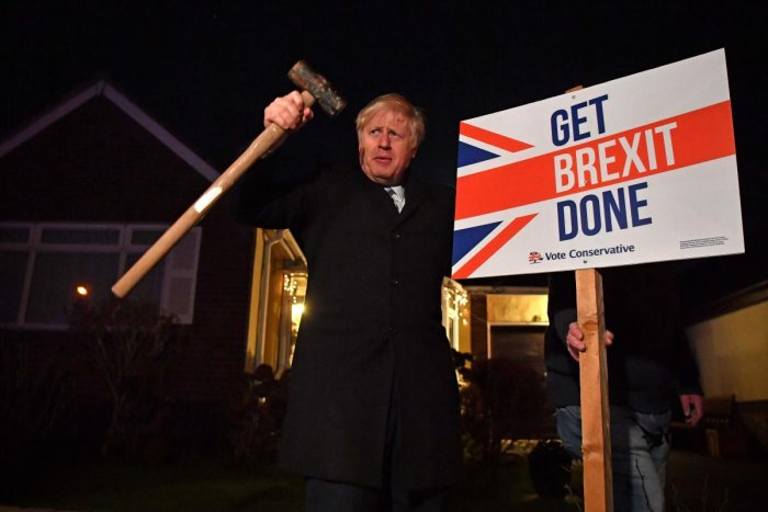 "In this file photo taken on December 11, 2019, Britain's Prime Minister and Conservative party leader Boris Johnson poses after hammering a ""Get Brexit Done"" sign into the garden of a supporter, with a sledgehammer as he campaigns with his team in Benflee"