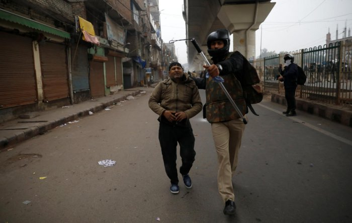 A police officer detains a demonstrator during a protest against a new citizenship law in Seelampur, area of Delhi