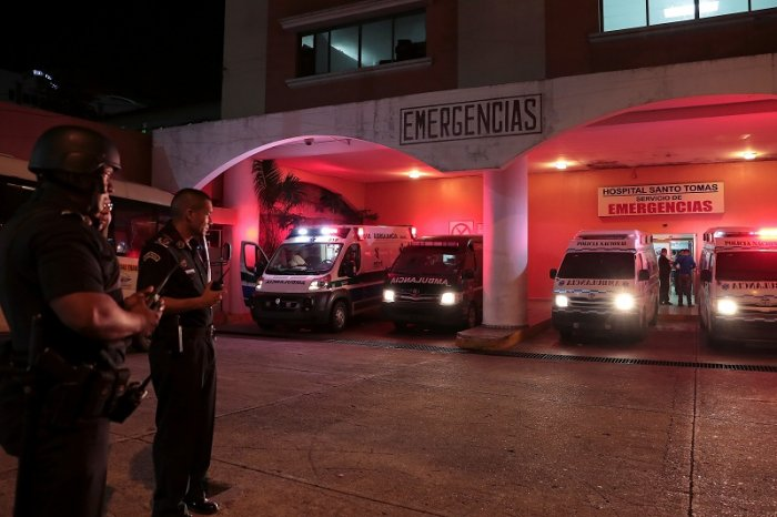 Police officers keep watch outside a hospital where injured inmates were taken following a shootout among inmates at La Joyita prison, in Panama City, Panama. (Reuters Photo)