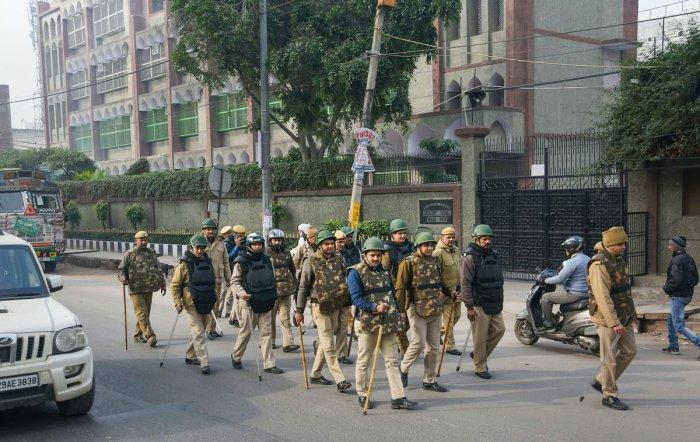 Delhi police personnel patrol a street. (PTI photo)