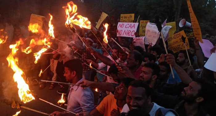 Students of the University of Mysore (UoM) stage a torchlight protest against Citizenship (Amendment) Act, at Manasagangothri, in Mysuru, on Tuesday evening.