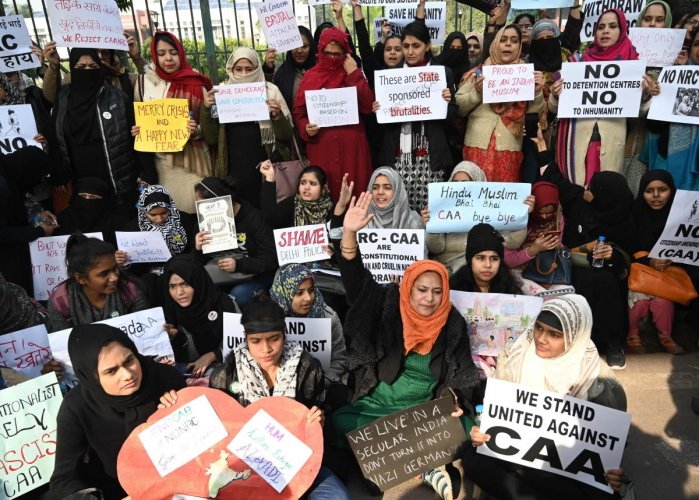 Students and supporters hold placards as they protest outside Jamia Millia Islamia university over India's new citizenship law in New Delhi on December 18, 2019. (Photo by AFP)