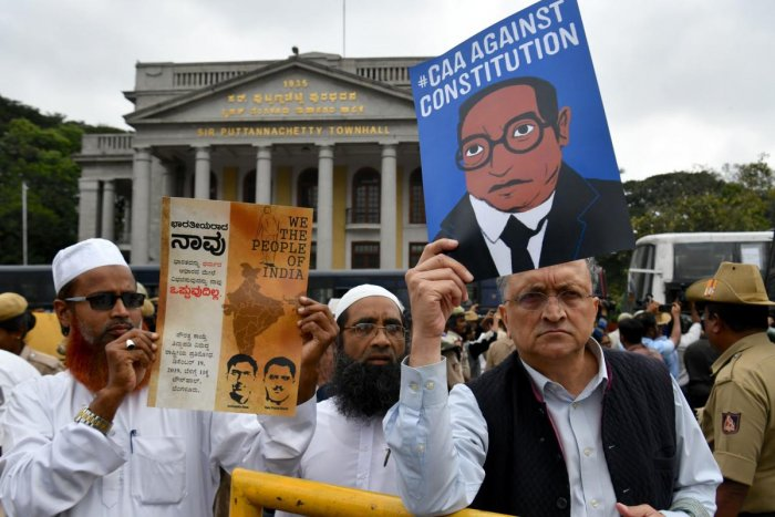 Historian Ramchandra Guha (R) holds a placard against India's new citizenship law during a protest held in spite of a curfew in Bangalore on December 19, 2019.