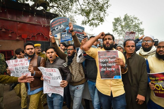 Protestors hold placards as they raise slogans during a demonstration against the Citizenship (Amendment) Act, at Red Fort in New Delhi, Thursday, Dec. 19, 2019. (PTI Photo)