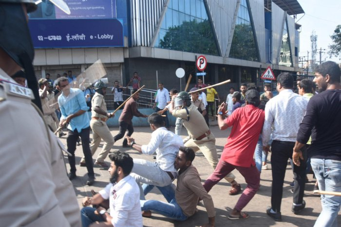Police cane protesters near DC's office in Mangaluru.