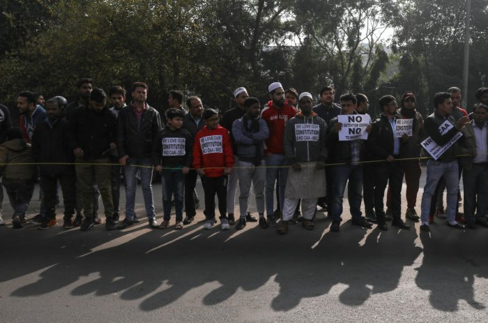 Demonstrators display posters during a protest against a new citizenship law, outside the Jamia Millia Islamia University in New Delhi. Reuters