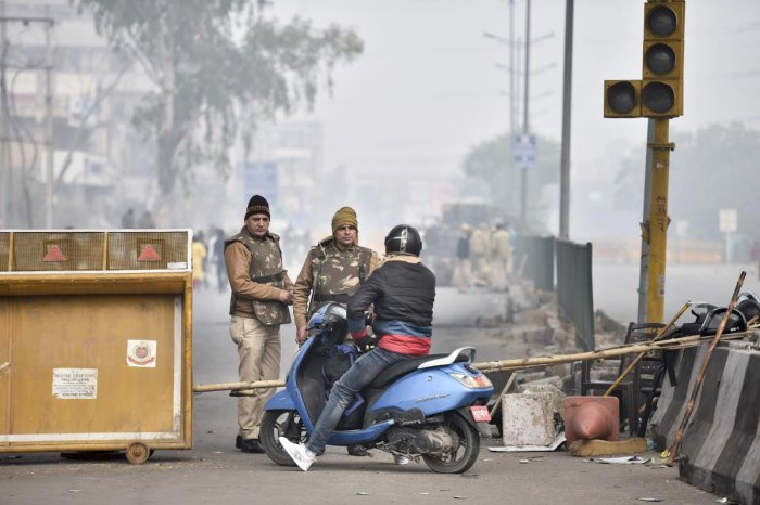 Police personnel stop a commuter as temporary barricades are set up during restrictions in view of protests against the Citizenship (Amendment) Act after Friday prayers, at Jamia Nagar, in New Delhi. (PTI photo)