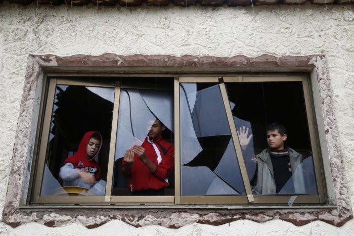 Palestinian boys pull shards of glass from a broken window at their home near the site of attacks by Israeli aircraft in the Hamas-controlled Gaza Strip. (AFP Photo)
