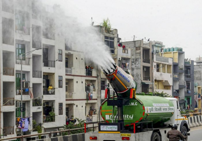 An East Delhi Municipal Corporation (EDMC) water tank with an anti-smog gun sprays water into the air to reduce pollution in New Delhi.