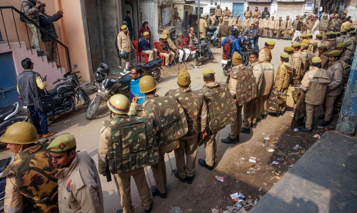 Police personnel guard a street during protests against Citizenship Amendment Act (CAA) in Varanasi. (PTI Photo)