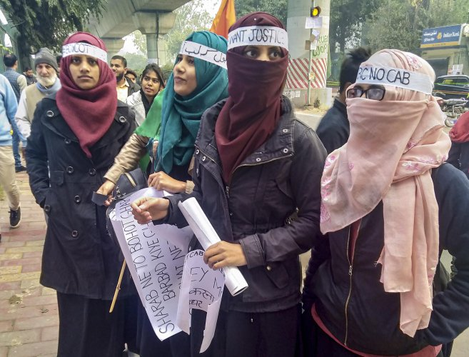 Protestors hold placards during a demonstration against the Citizenship Amendment Act (CAA) outside Jamia Milia Islamia University. (PTI Photo)