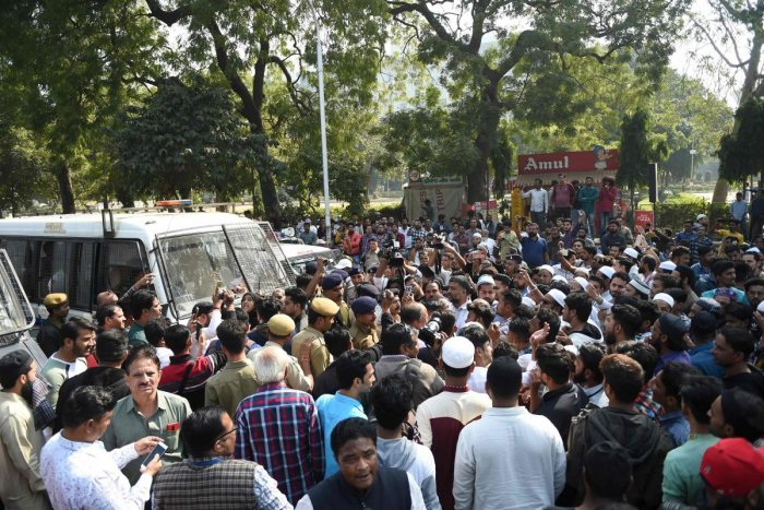 Protesters stop a police vehicle with detainees inside during a demonstration against India's new citizenship law in Ahmedabad