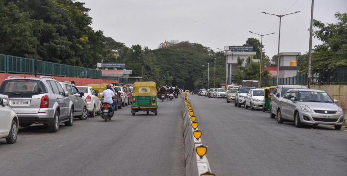 Commuters complain that cars parked on the either side of the road on Ambedkar Veedhi, in front of the City Civil Court, have narrowed the stretch leading to traffic jams. DH photo/S K Dinesh