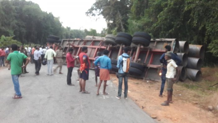 A trailer carrying huge pipes toppled and fell on the car crushing it instantaneously at Paravara Kotya near Udane on NH 75 in Shiradi Ghat on Friday evening.