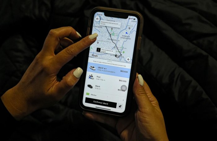 A woman checks the Uber transport application on her mobile phone after authorities ordered its suspension in Colombia. Photo/AFP