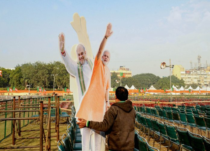 A workers carries cut-outs of Prime Minister Narendra Modi and Union Home Minister Amit Shah on the eve of  BJP rally at Ramlila Maidan in New Delhi. (PTI Photo)