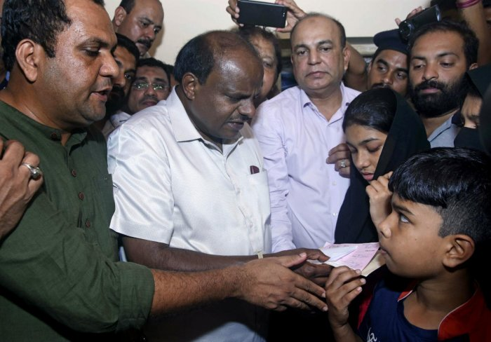 Former chief minister H D Kumaraswamy hands over a cheque of Rs 5 lakh to the children of Ahmmed Jaleel, who was killed in police firing, at his residence at Kandak, in Mangaluru on Sunday. DH Photo