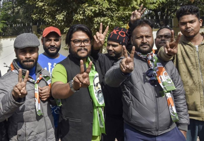 Jharkhand Mukti Morcha (JMM) and Congress Party workers flash victory sign during the counting of votes for Jharkhand Assembly Elections results. (PTI photo)