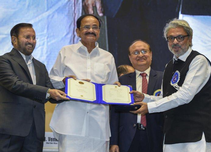 ice-President Venkaiah Naidu and Union Minister Prakash Javadekar present the best music director award to Sanjay Leela Bhansali for his movie 'Padmavaat ' during the 66th National Film Awards function in New Delhi, Monday, Dec. 23,2019. (PTI Photo)