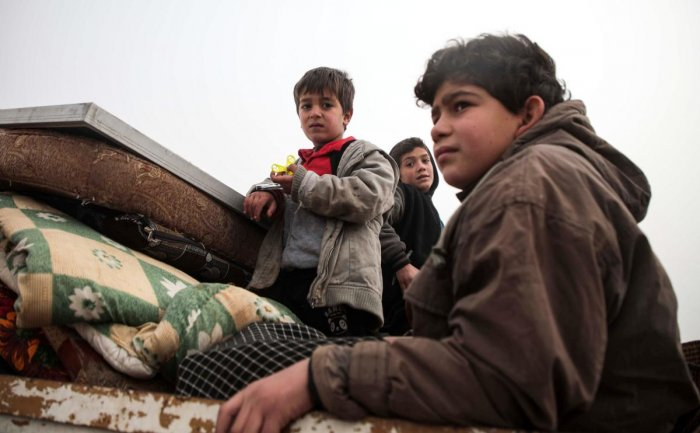 Syrian children look on while riding in the back of a truck as part of a convoy of people from the south of Idlib province fleeing bombardment by the government and its allies on the northwestern region, heading northwards along a highway near Sarmada on December 22, 2019. (Photo by Aaref WATAD / AFP)