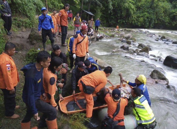 In this photo released by the National Search And Rescue Agency (BASARNAS), rescuers remove the body of a victim of a bus accident in Pagaralam, Indonesia, Tuesday, Dec. 24, 2019.(AP Photo)