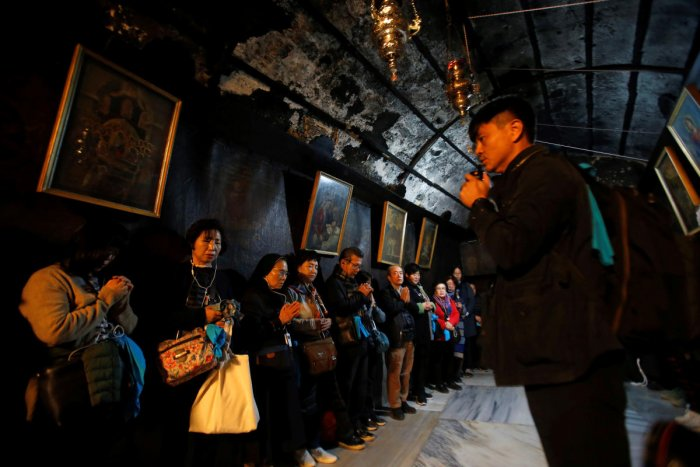 Worshippers pray inside the Church of the Nativity on Christmas eve in Bethlehem, in the Israeli-occupied West Bank